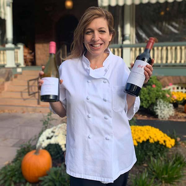 Rebecca holding wine bottles in front of restaurant